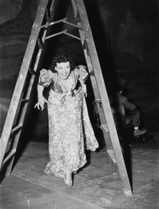 Woman walking under a step ladder with her fingers crossed