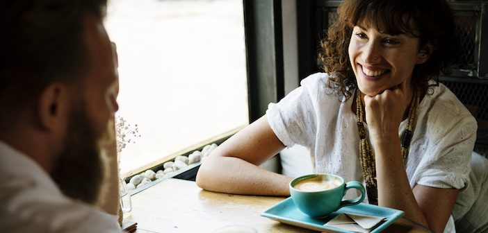two people sitting in a cafe at a table drinking coffee smiling