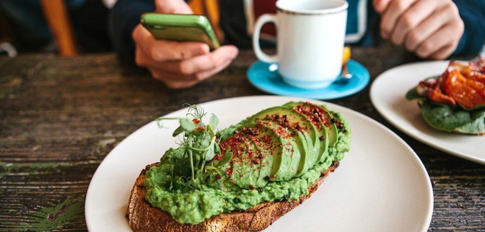 Sandwich with avocado on a wooden table. A man is going to call or write a message to another person in the background