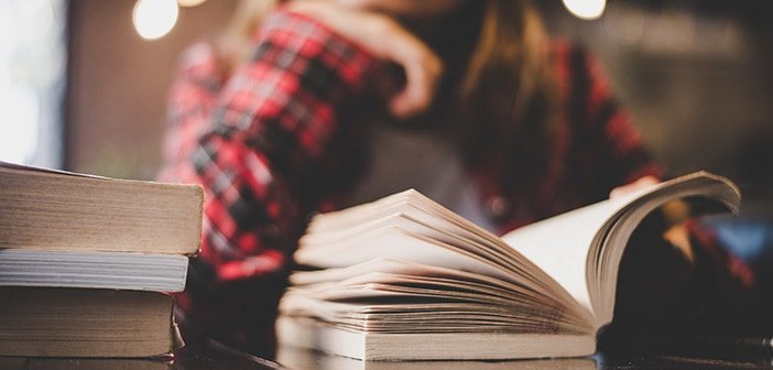 Hipster woman teenager sitting enjoy reading book at cafe.