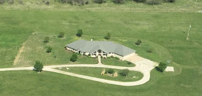 aerial view of large home on big piece of land