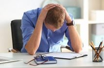 seated man looking down with hands on back of head and elbows on desktop worried, sad or frustrated at work