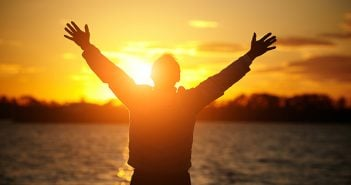 silhouette of man standing in front of water during sunset with hands stretched overhead symbolizing gratitude
