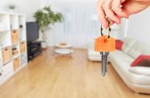 person holding house key with living room in background