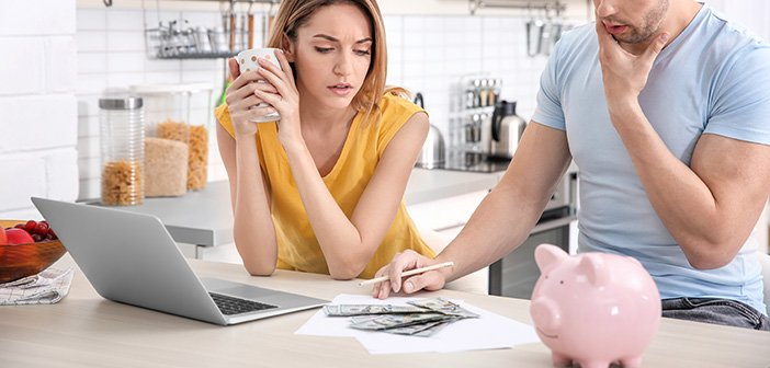 young couple looking over financials in kitchen on computer and printed papers with piggy bank and money in view