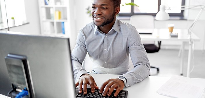man sitting at desk working on a computer