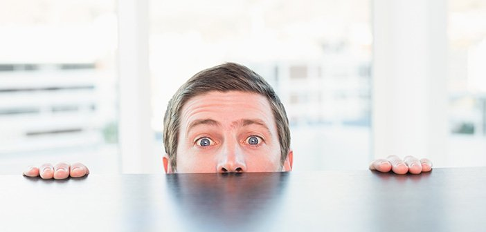 Nervous businessman peeking over desk