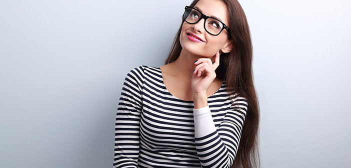 Pretty casual thinking woman in glasses looking up on blue background with empty copy space