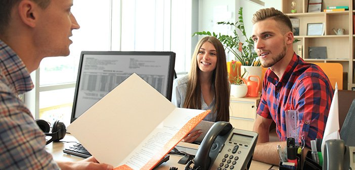 happy family at desk signing papers with real estate agent