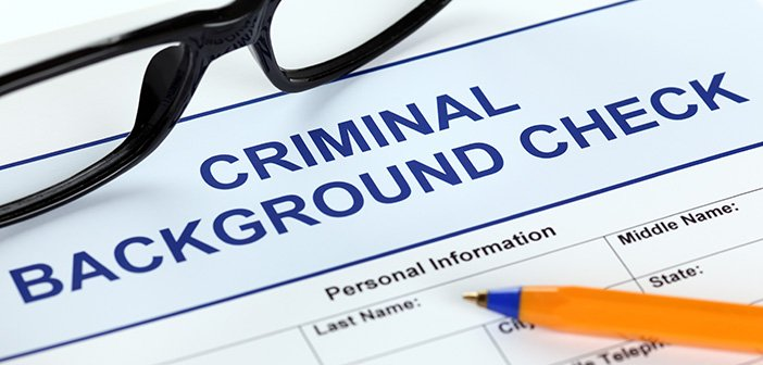 Criminal background check application form with glasses and ballpoint pen.