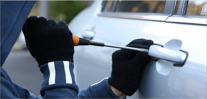 thief breaking into a car using screwdriver to unlock door