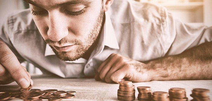 bearded man wearing white shirt hovered over pile of pennies counting them