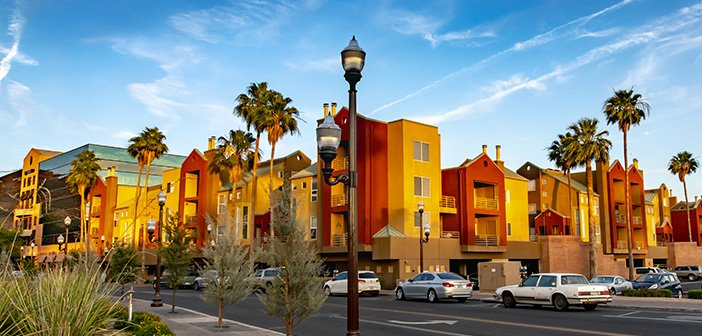 vivid red and yellow apartment building with palm tree-lined property against blue sky background