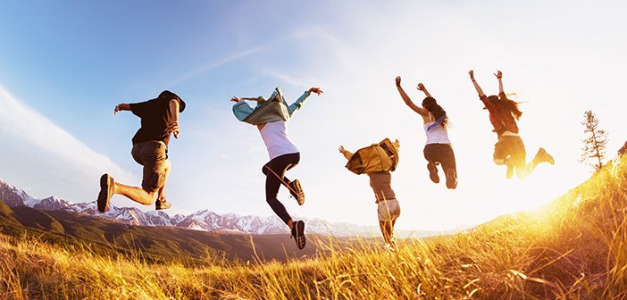 Group of five happy friends runs and jumps against mountains at sunset time. Travel or expeditions concept