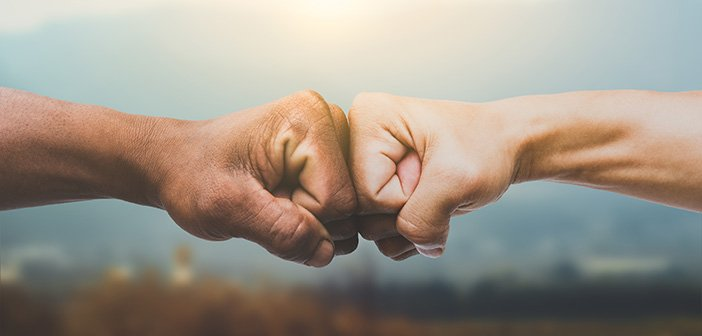 Man giving fist bump in sun rising nature background. power of teamwork concept. vintage tone