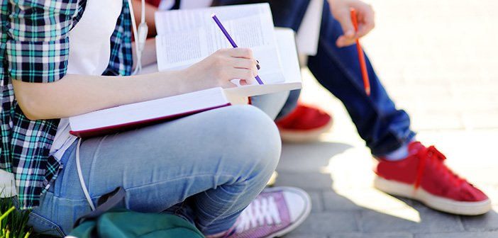 Close up photo of young happy students with books and notes outdoors. Smart young guy and girl in University campus. Learning and education for young people.