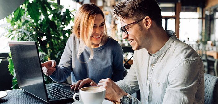 Attractive man in eyeglasses and charming woman is pointing at the laptop screen, laughing together, resting at cafe with cup of coffee.
