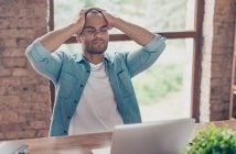 Stressed sick mulatto freelancer is having headache and thinking how to finish his work. He is in a casual smart, at his home office