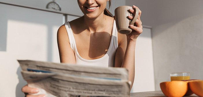 Smiling young girl standing at the kitchen in the morning, reading newspaper, drinking tea