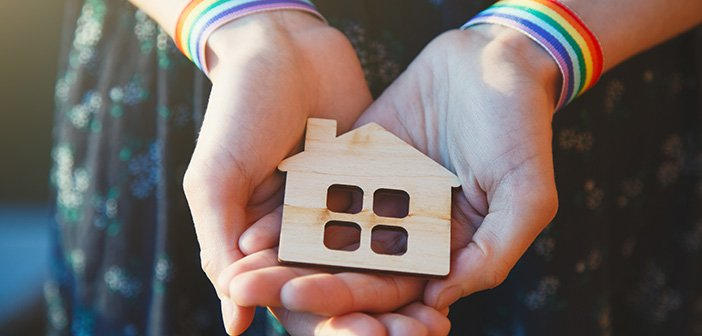 young female hands with LGBT rainbow ribbon wristbands holding craft wooden house