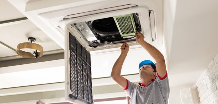 man on ladder installing air conditioning unit in ceiling opening