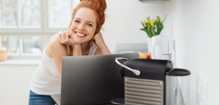 Young woman relaxing in a kitchen with a laptop computer balanced on the counter looking over the top to smile happily at camera