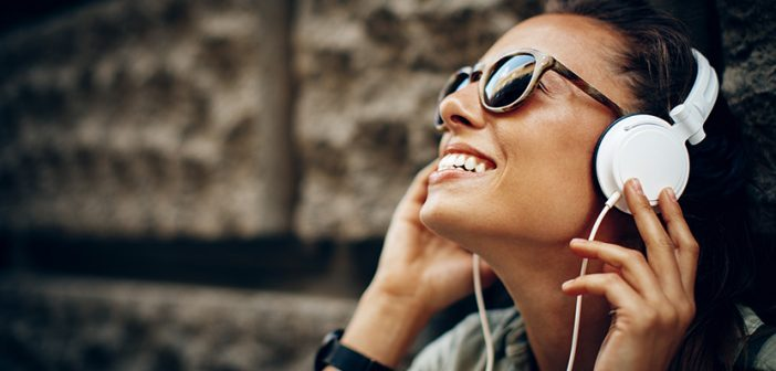 smiling dark haired girl listening to white headphones and smiling sitting outside in urban setting