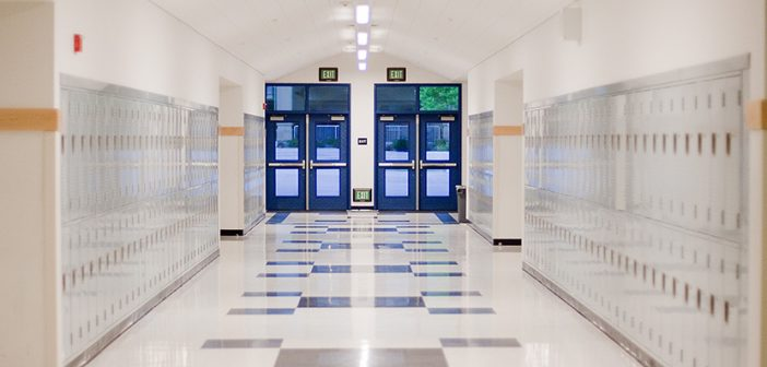 brightly lit school hallway with light gray lockers and blue doors with window leading outside