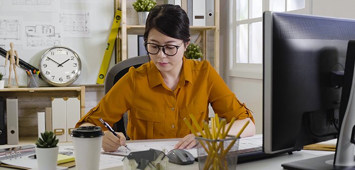 professional young asian female architect wearing casual shirt sitting in cozy office and making architectural sketches. Profession concept. beautiful young girl interior designer drawing blueprint.