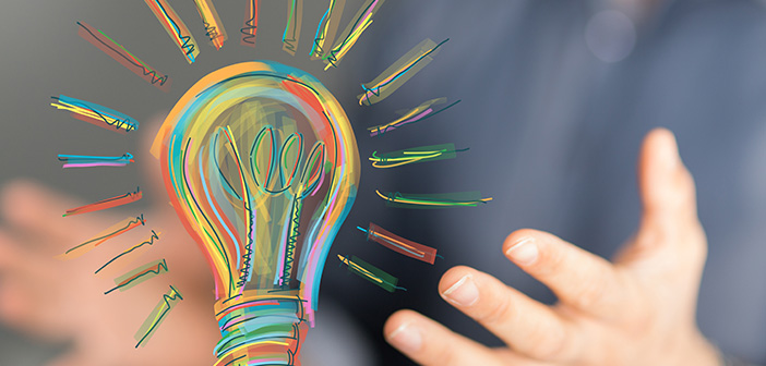 close up of man's hands hovering under colorful drawing of lightbulb