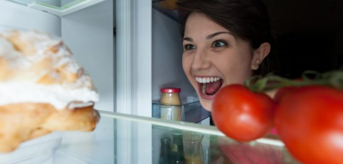 woman looking in refrigerator with menacing grin at dessert