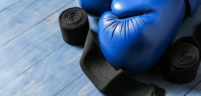 Boxing gloves and wrist bands on wooden background