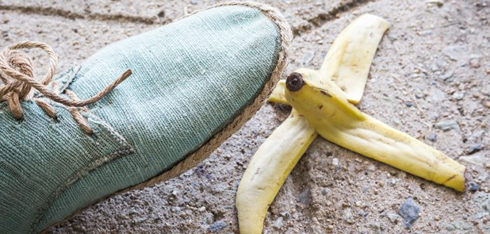 light turquoise canvas shoe about to step on banana peel on sidewalk