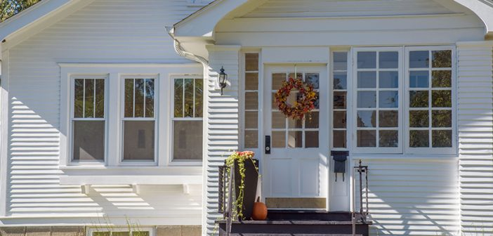 Exterior street view of cute bungalow home decorated for fall wi