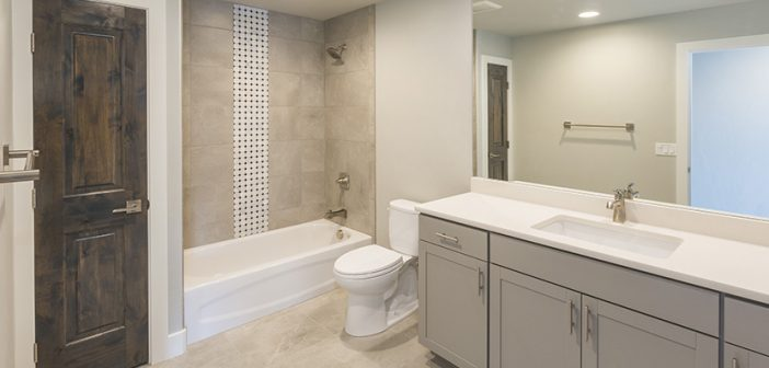 luxury bathroom remodel with gray tiled shower light gray cabinetry white walls and light vinyl flooring
