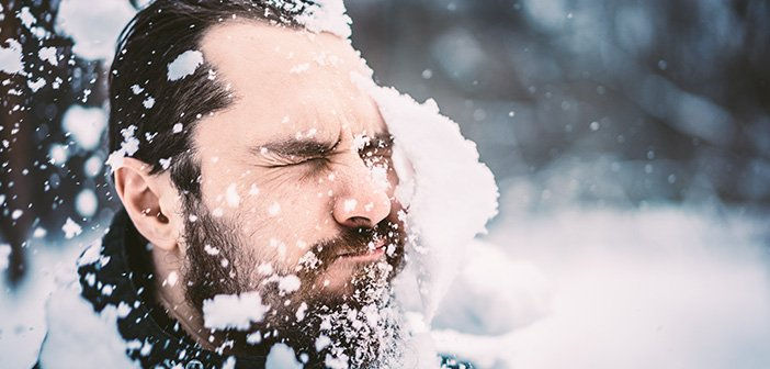 dark-haired bearded man getting hit in the face with a large snowball outside during winter