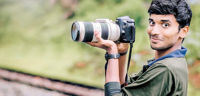 man in nature holding up SLR camera with telephoto lens