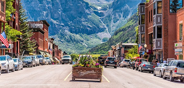 Telluride, Colorado - small town village in Colorado with sign for city and flowers by historic architecture on main street mountain view