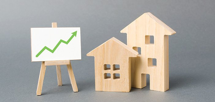 Two wooden houses and a green up arrow on the sign. Real estate value increase. Rising prices for housing, building maintenance. High rates of construction, high liquidity. Supply and demand